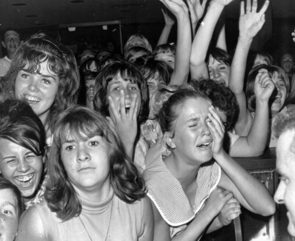 **FILE**Just the sight of The Beatles from a distance caused this reaction among a group of Girls at the Los Angeles International airport in this Aug.18, 1964 file photo. Airport security kept the British singers away from several thousand youngsters during a brief stopover in Los Angeles en route to San Francisco. (AP Photo/stf)