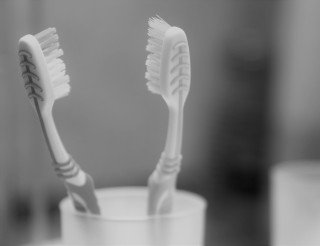 Two toothbrushes in the glass. Close up shot of toothbrush.